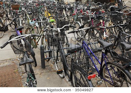 Many different bicycles with baskets are parked in cycle parking