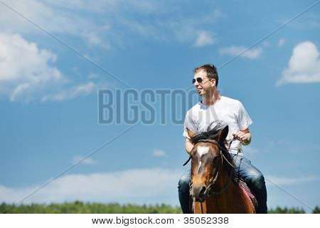 young man ride horse farm animal with blue sky in background