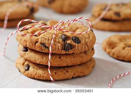 Freshly baked chocolate chips cookies tied with festive baker's twine and stacked on parchment paper.  Macro with extremely shallow dof.