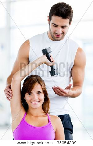 Fit woman at the gym with a personal trainer