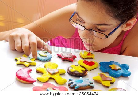 Young girl picking up one of many colorful and delicious cookies on a white table
