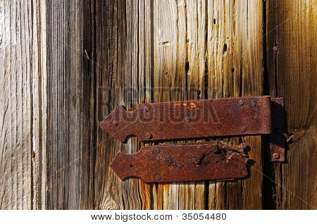 Detail of a closed wooden old door with big rusty iron hinge