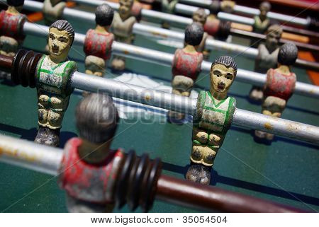 Closeup on miniature metallic ball players of a Foosball table game