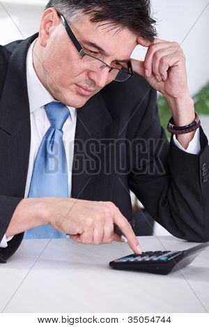 Worried senior businessman calculating, unsatisfied with result