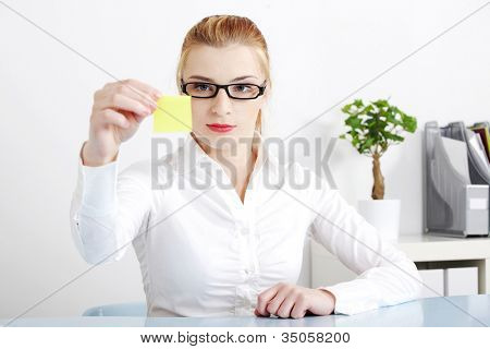 Young woman sitting at desk in office with yellow post-it sticker in her hand. Blond businesswoman in glasses and white shirt looking at the paper with important information to remember.