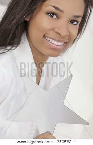 Portrait of a beautiful young African American woman smiling, relaxing and holding a silver star