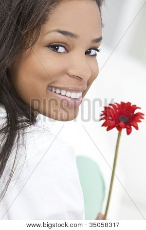 Beautiful happy young African American woman or girl smiling and holding a red flower