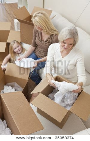 Female generations of a family, mother, daughter & grandmother unpacking boxes and moving into a new home.