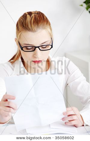 Young businesswoman sitting at desk in office and holding sheet of paper Blond girl in white shirt and black glasses focused and concentrated on reading document.