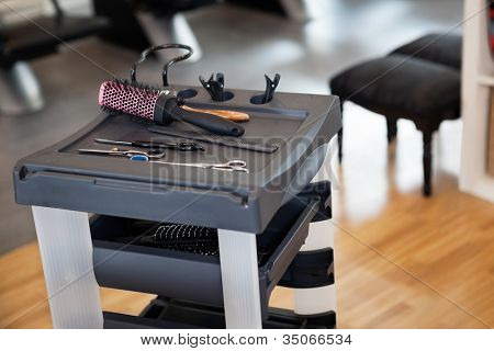 Set of hairbrush, comb and scissors on trolley in parlor