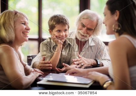 Happy Parents And Grandparents With Boy In Bar
