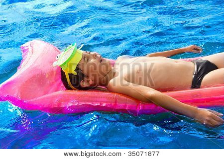 Boy Swimming On The Water With Relaxation