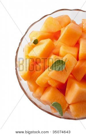 Fresh melon cubes with mint leaves in bowl