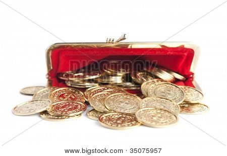 Scattered gold coins are in open hot red purse, isolated on white background. A great number of coins symbolize wealth, richness, income and profit. Close up shot.