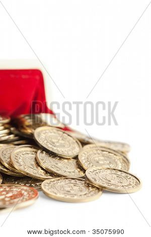 Scattered gold coins are in hot red partly viewed purse, isolated on white. A great number of coins symbolize wealth, richness, income and profit. Close up shot.