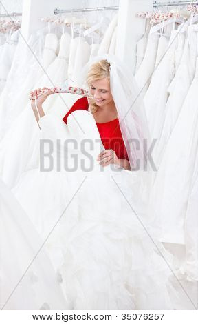 Bride is looking forward to try wedding dress on, on white background.