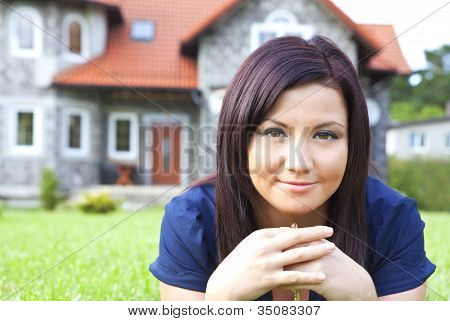 Woman Holding Keys With House In Background
