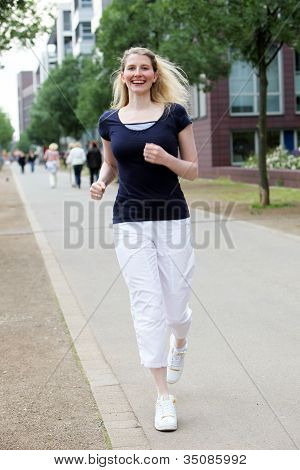 Woman Jogging Along An Urban Sidewalk