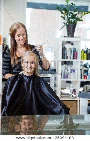 Mirror reflection of beautician applying color dye to woman's hair at parlor