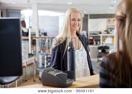 Young blonde woman standing by cash counter at hair salon