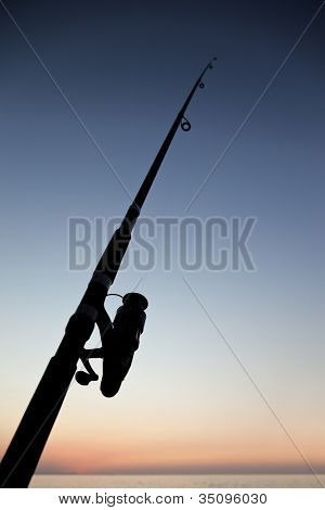 Fisherman sport hobby fishing rod or spinning reel on sea beach sunset
