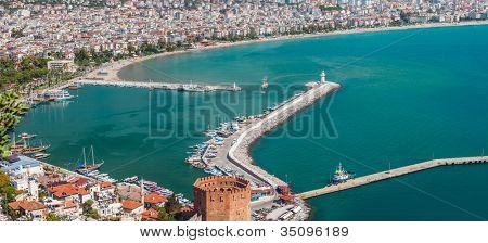 Summer vacations - blue Mediterranean sea and Turkey Alanya east coast beach resort with lighthouse and ship bay view from ancient mountain castle wall