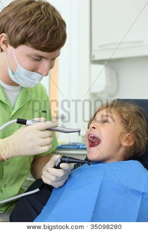 Young dentist holds saliva suction and grinding drill, happy girl opens her mouth in dental clinic.