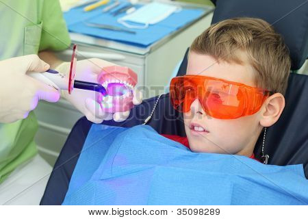Patient boy in orange protective glasses looks how ultraviolet curing light tool affects at artificial jaw