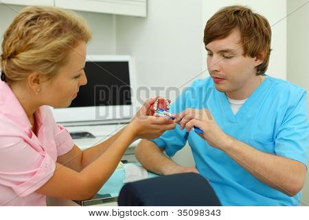 Dentists show how to correctly brush teeth. For clarity, doctors use an artificial jaw. Focus on hands.