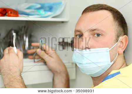 Dentist in mask holds metal dental instruments and looks at camera.