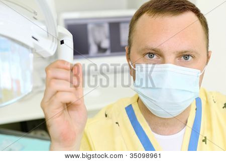 Dentist in mask clings to lamp in dental clinic and looks at camera.