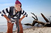 foto of bare chested  - Ragged castaway pirate on beach bares his teeth and leans forward defending treasure chest nearby - JPG