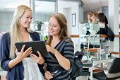 stock photo of beauty parlor  - Young female customer holding digital tablet while standing with hairdresser at parlor - JPG