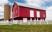 stock photo of red siding  - Red painted wooden barn with white door on farm in traditional US style - JPG