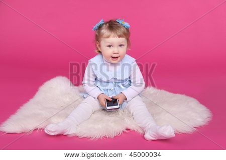 Funny Little Girl Playing With Mobile Phone Over Pink Background