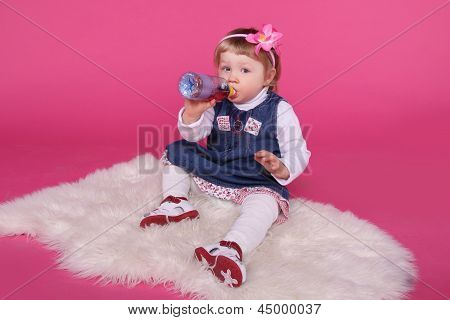 Portrait Of Funny Little Girl Drinking Water Sitting On Fur Over Pink Background