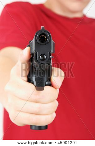 Teenager with a gun in his hand, focus on the gun