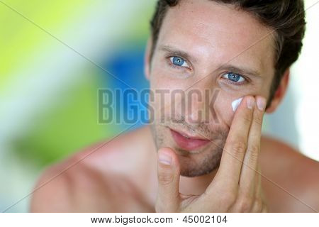 Homem bonito, aplicar creme hidratante