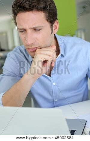 Man with doubtful look in front of laptop