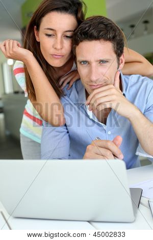 Couple looking at laptop with perplexed expression