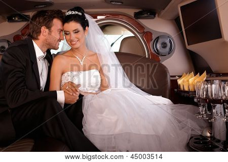 Beautiful young couple sitting in limousine on wedding-day, smiling.