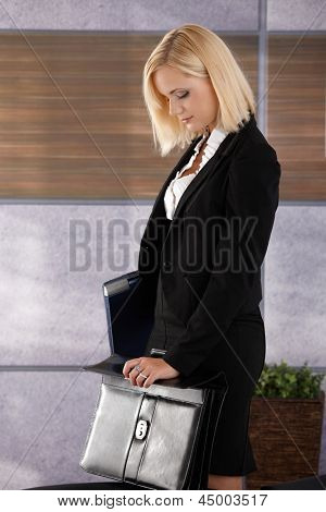 Attractive businesswoman standing in office, holding laptop computer and closing business briefcase.