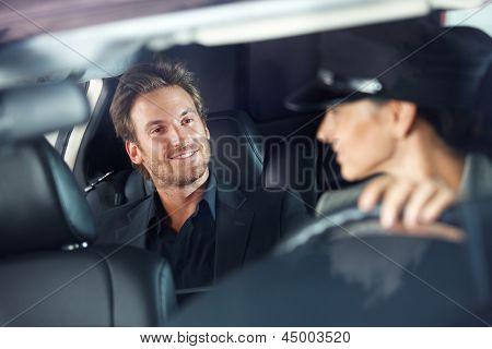Handsome man sitting in luxury car, female chauffeur driving.
