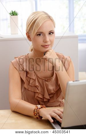 Portrait of blond office worker woman sitting at desk, using laptop computer, looking at camera.