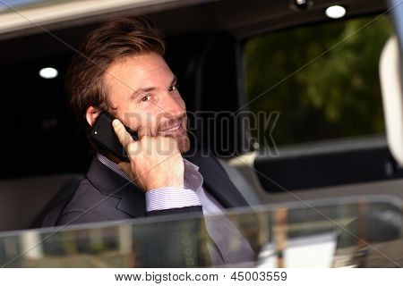 Handsome young businessman on phone call, sitting in elegant car.