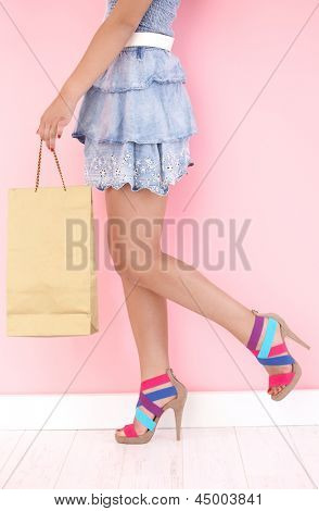 Pretty girl with shopping bag and high heels.