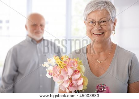 Portrait of smiling senior woman holding flowers, man at background.