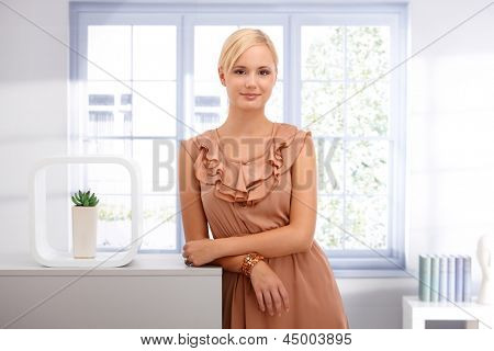 Portrait of attractive smart blond woman standing in elegant bright living room, smiling at camera.