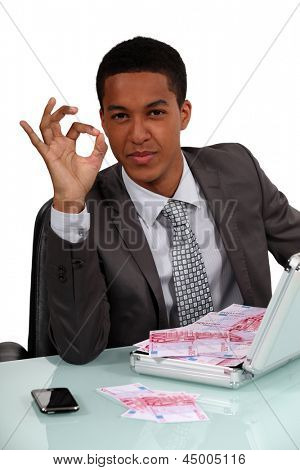 businessman holding a briefcase full with money and making an okay sign