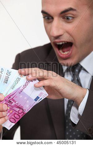 empresário segurando um monte de dinheiro em numerário